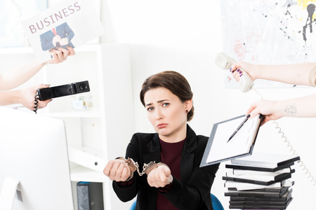 sad businesswoman showing hands with handcuffs while secretaries holding newspaper, telephones and clipboard in office Stock Photo