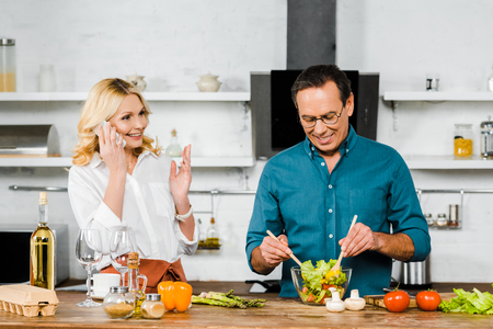 attractive mature wife talking by smartphone and handsome husband mixing salad in bowl in kitchen Standard-Bild - 116707996