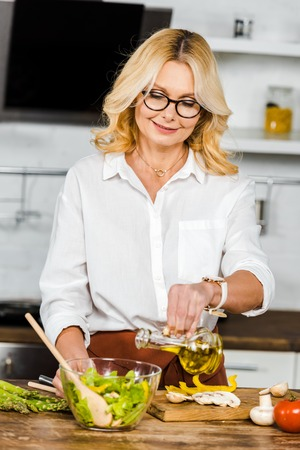 attractive mature woman pouring oil into bowl with salad in kitchen Stockfoto