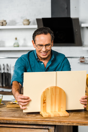 smiling handsome mature man cooking in kitchen and taking cookbook