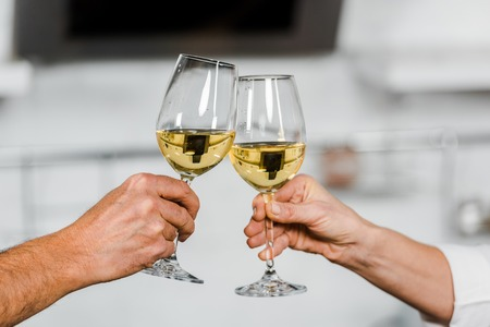 cropped image of wife and husband clinking with glasses of white wine in kitchen 免版税图像