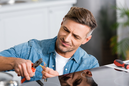 handsome man repairing electric stove at kitchen with pliers