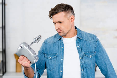 confused handsome man looking at kitchen mixer