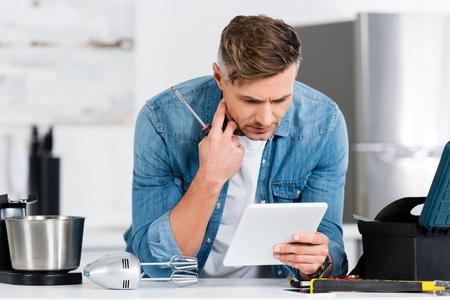 handsome man using digital tablet white repairing kitchen mixer Stock Photo