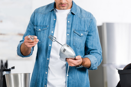 cropped view of man holding kitchen mixer and whisk Stock fotó