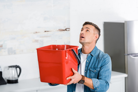 handsome man holding plastic bucket and looking at ceiling