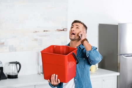 man talking on smartphone while holding plastic bucket and looking at leaking water from ceiling Stock Photo
