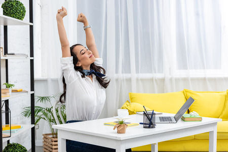 Tired asian freelancer stretching on chair with raised hands while sitting at work desk at home Stockfoto