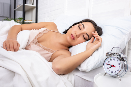 Beautiful young woman in elegant nightie sleeping on white bedding while alarm clock showing quarter to eight in morning