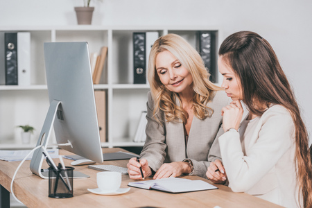 smiling female business mentor pointing at notebook and working with young colleague in office Foto de archivo