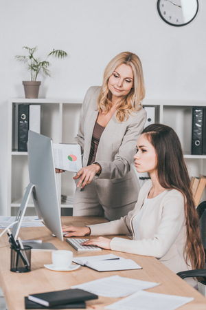 young businesswoman using desktop computer and mature female mentor pointing at screen