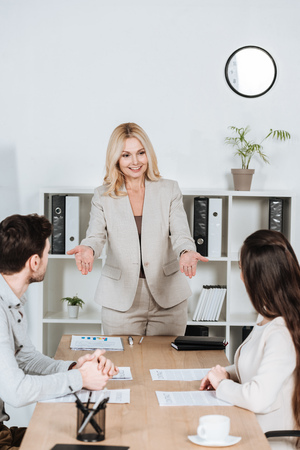 smiling female business mentor looking at young colleagues sitting at workplace Foto de archivo