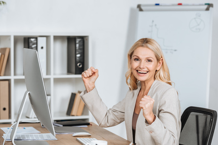 excited businesswoman shaking fists and smiling at camera while sitting at workplace