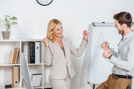 excited young businessman and mature businesswoman triumphing and shaking fists in office