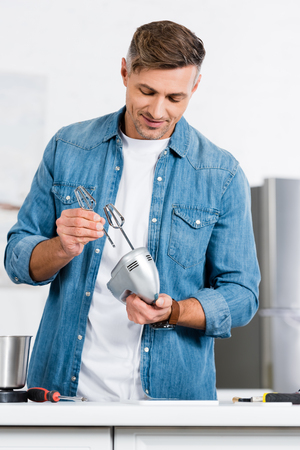 cropped view of man putting whisk into kitchen mixer
