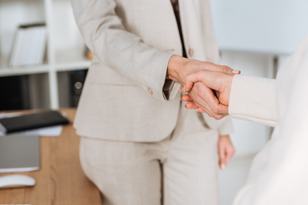 close-up partial view of professional businesswomen shaking hands in office Imagens