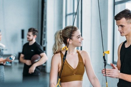 young male trainer looking at smiling sport girl exercising with resistance bands in gym