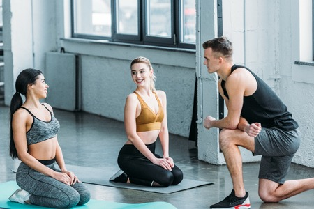 handsome male trainer looking at smiling multiethnic girls in sportswear training on yoga mats in gym Standard-Bild
