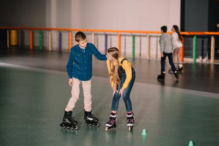 Joyful kids practicing roller skating on rink together Stock Photo