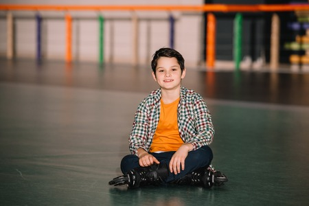 Brunette boy in roller skates sitting on roller rink Stock Photo