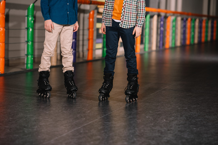 Partial view of boys in black roller skates posing on rink Stock Photo