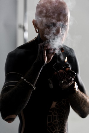 handsome shirtless man with tattoos smoking cigar on grey Stok Fotoğraf