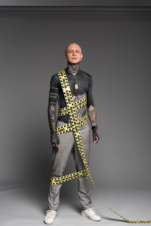 full length view of bald shirtless tattooed man with police line around body looking at camera on grey Reklamní fotografie