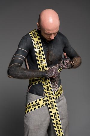 Homme tatoué torse nu chauve avec une ligne de police autour du corps regardant les poings isolés sur gris