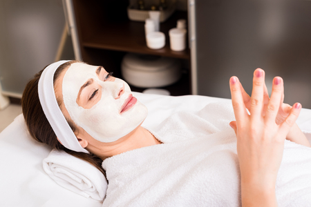 woman lying in white bathrobe with applied facial mask at beauty salon Stock fotó