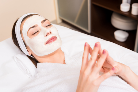 woman lying in white bathrobe and hairband with applied facial mask at beauty salon Stock fotó
