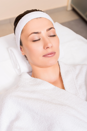woman lying in white bathrobe with closed eyes at beauty salon