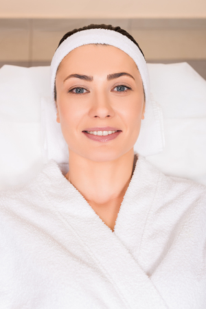 top view of woman lying and smiling in white bathrobe at beauty salon 写真素材