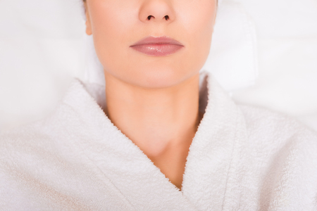 cropped view of woman lying in white bathrobe at beauty salon 写真素材
