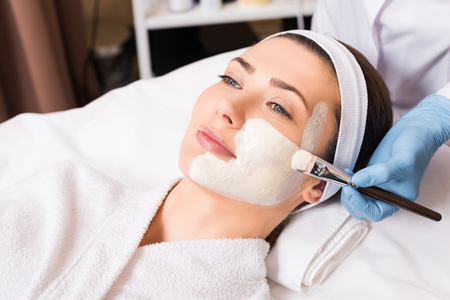 beautician applying cosmetic mask on part woman face with cosmetic brush at beauty salon 写真素材