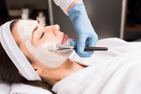 beautician applying cosmetic mask to woman on face at beauty salon