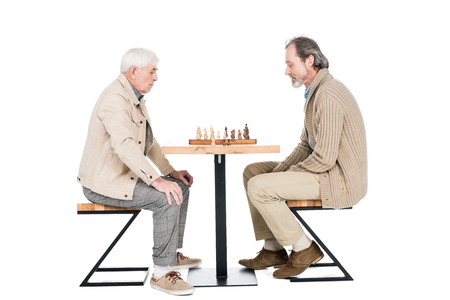 retired men playing chess while sitting isolated on white
