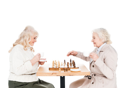cheerful retired women playing chess isolated on white