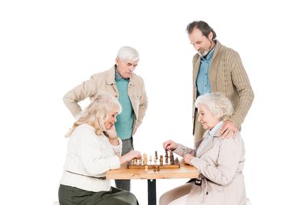 retired women playing chess near senior men isolated on white Banco de Imagens - 116706119