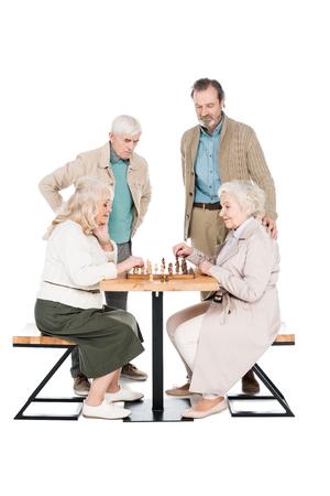 happy senior women playing chess near retired men isolated on white