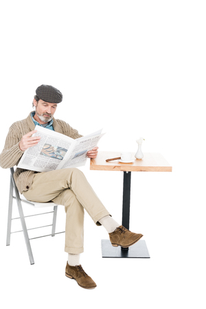 senior man reading newspaper while sitting on chair with crossed legs isolated on white