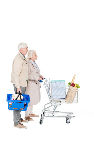 retired husband and wife walking with shopping trolley and basket isolated on white