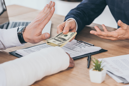 cropped view of worker rejecting money giving businessman in blue jacket at table in office, compensation concept Stock Photo