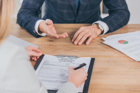 cropped view of woman signing form for compensation claim and sitting opposite to businessman in office, compensation concept