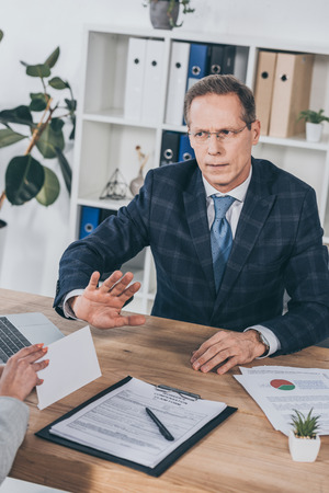 businessman in blue jacket sitting at table and rejecting envelope giving by woman in office, compensation concept