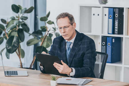 middle aged businessman sitting at table, holding documents and reading in office, compensation concept Zdjęcie Seryjne