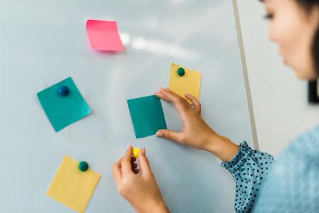 Vista recortada de la mujer poniendo coloridas notas adhesivas en la pizarra en la oficina