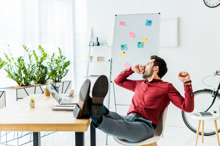 tired businessman with legs on table yawning in office