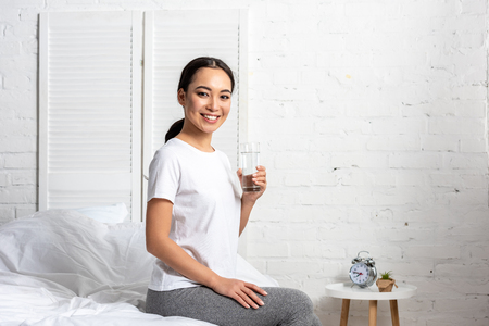 Beautiful smiling asian girl in white t-shirt sitting on bed with glass of water