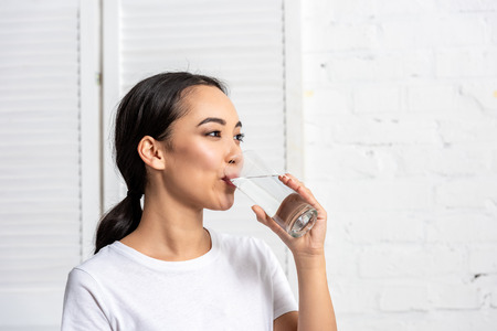 Beautiful young asian woman drinking water in morning