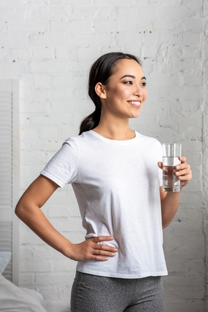 smiling young asian  woman holding glass of water, standing in bedroom with hand on hip Stockfoto